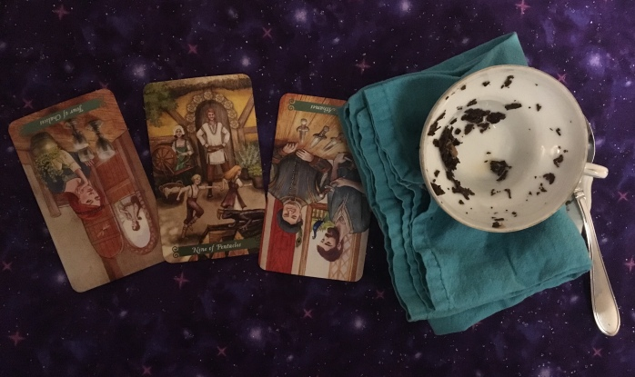 A tea cup with leaves and a three-card tarot spread.